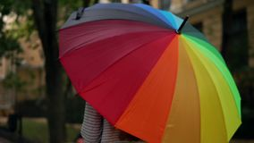Closeup view of an open spinning colourful rainbow umbrella in female hands. Slowmotion shot