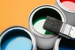 Closeup view of paint cans and brush. On color background stock image