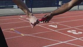 Closeup view of participant handing off baton to next runner, world championship