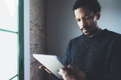 Closeup view of pensive bearded African man using tablet while standing near the window in his modern apartment.Concept royalty free stock photo
