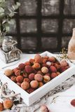 Closeup view of pile of lychees in wooden box. On wooden table stock images