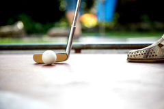 Closeup view from a professional minigolf player hitting a white. A closeup view from a professional minigolf player hitting a white ball with an iron racket Royalty Free Stock Photo