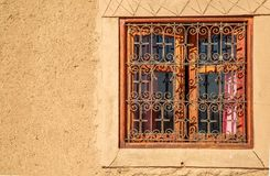 Rammed earth wall with traditional wrought iron window. Closeup view on Rammed earth wall with traditional wrought iron window Royalty Free Stock Images