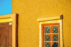 Rammed earth wall with traditional wrought iron window. Closeup view on Rammed earth wall with traditional wrought iron window Stock Photography