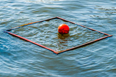 Closeup view of a red bouy within the floating square frame Royalty Free Stock Photos