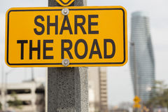 closeup view of the road yellow sign with written words against city background Royalty Free Stock Photo