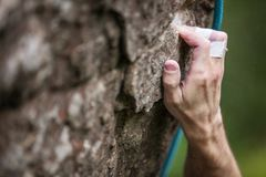Rock climber`s hand gripping hold on cliff Stock Photography