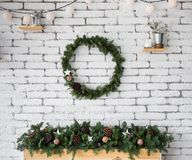 Round elegant Christmas wreath hanging on white brick wall Royalty Free Stock Photography