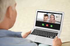 Closeup view of senior man talking with grandchildren via video chat. Closeup view of senior men talking with grandchildren via video chat at home stock images