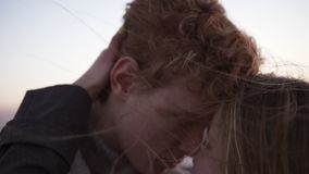 Closeup view of sensual woman standing with relaxed young red head man touching and stroking his from hand to shoulder stock video footage