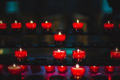 A closeup view of several lit red candles put together on a dark royalty free stock image