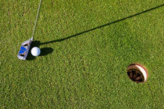 Closeup view of a short putt. Closeup photo of a short putt. Overhead viewpoint, nobody in the image, with long morning shadows Royalty Free Stock Photos