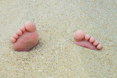 Closeup view of small  feet with toes in the sand lit by the sunset light Stock Image