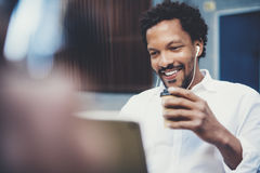 Closeup view of Smiling african man using smartphone to listen to music while sitting on the bench at sunny street Royalty Free Stock Photography