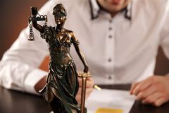 Closeup view of Statue Of Justice. Man in the white shurt on the background. Closeup view of Statue Of Justice. Man in the white shurt on the background royalty free stock image