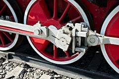 Closeup view of steam locomotive wheels, drives, rods, links and. Other mechanical details. White, black and red colors Stock Photos