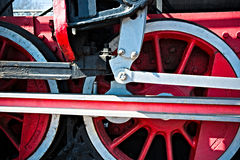 Closeup view of steam locomotive wheels, drives, rods, links and. Other mechanical details. White, black and red colors Stock Photo