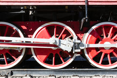 Closeup view of steam locomotive wheels, drives, rods, links and. Other mechanical details. White, black and red colors Stock Photography