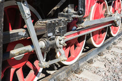 Closeup view of steam locomotive wheels, drives, rods, links and. Other mechanical details. White, black and red colors Stock Images
