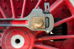 Closeup view of steam locomotive wheels, drives, rods, links and. Other mechanical details. White, black and red colors Royalty Free Stock Images