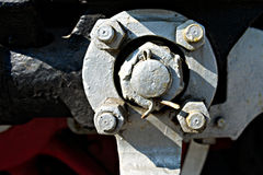 Closeup view of steam locomotive wheels, drives, rods, links and. Other mechanical details. White, black and red colors Royalty Free Stock Image