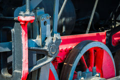 Closeup view of steam locomotive wheels, drives, rods, links and. Other mechanical details. White, black and red colors Stock Image