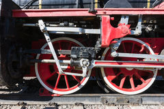 Closeup view of steam locomotive wheels, drives, rods, links and. Other mechanical details. White, black and red colors Royalty Free Stock Photos