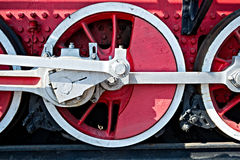 Closeup view of steam locomotive wheels, drives, rods, links and. Other mechanical details. White, black and red colors. Brakes system Royalty Free Stock Images
