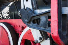 Closeup view of steam locomotive wheels, drives, rods, links and. Other mechanical details. White, black and red colors. Link motion Stock Image