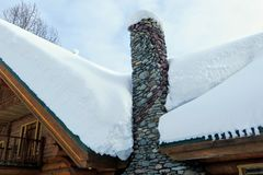 A closeup view of a stone chimney attached to a remote log cabin covered in freshly fallen snow. royalty free stock image
