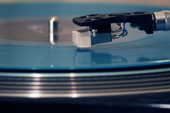 Closeup view of a stylus that traces the groove on a rotating vinyl record on a phonograph. The motion of stylus are converted into an analogous electrical Stock Photography