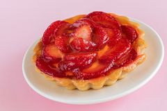 Closeup view of tartlet with vanilla cream covered with slices of strawberry. stock photos