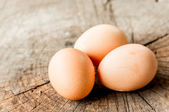 Closeup view of three brown eggs on the wood stock image