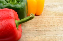 Closeup view of three coloured peppers on wooden plank Stock Photography