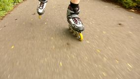 A closeup view to legs in white rollerblades. The man is quickly blading on asphalt way in park stock video