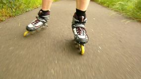 A closeup view to legs in white rollerblades. The man is quickly blading on asphalt way in park stock video footage