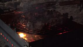 Closeup view to Meat barbecue on metall grill with smoke and fire at night