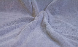 Closeup view of towel. Closeup view of blue towel. Fluffy gray background Royalty Free Stock Images