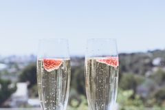 Closeup view of Two beautiful champagne glasses with strawberry on sunny terrace outdoor. Summer day outside of the city. stock images
