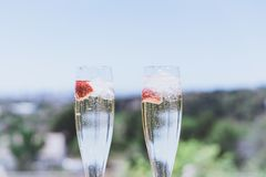 Closeup view of Two beautiful champagne glasses with strawberry on sunny terrace outdoor. Summer day outside of the city. royalty free stock photos