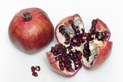 The closeup view of two pomegranates. The whole and split isolated on white background Stock Image