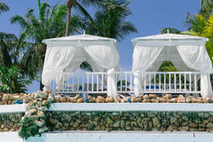 Closeup view of two white cozy gazebos in tropical garden on sunny gorgeous day Royalty Free Stock Photos