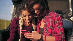 Closeup view of two young attractive girlfriends sitting inside of the open car trunk in the parking by the shopping. Mall and talking, looking at the picture stock video