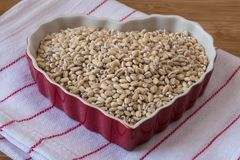 Dry Hulled Barley in heart shaped bowl. A closeup view of uncooked hulled barley in a red heart shaped bowl Royalty Free Stock Photography