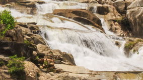 Closeup view of waterfall among rocks in park. Closeup view of waterfall cascade among rocks in tropical park stock video footage