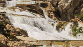 Closeup view of waterfall among rocks in park. Closeup view of waterfall cascade among rocks in tropical park stock video