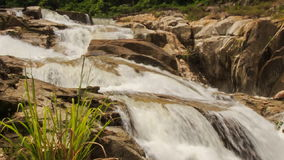 Closeup view of waterfall among rocks in tropical park stock video