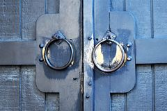 Door knocker on building in Quechee Village, Town of Hartford, Windsor County, Vermont, United States. Closeup view of weathered door knocker on a wooden blue stock images