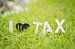 Closeup view white wood alphabet i love tax. black love symbol o Royalty Free Stock Photos