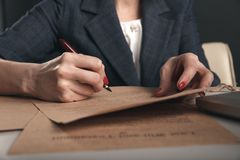 Closeup view of woman attorney writing on documents by pen. Closeup view of woman attorney writing on documents by pen stock image